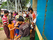 26 OCTOBER 2015 - YANGON, MYANMAR: People clamor to get off and on a Yangon Circular Train in the Da Nyin Station, about 90 minutes from Yangon. The Yangon Circular Railway is the local commuter rail network that serves the Yangon metropolitan area. Operated by Myanmar Railways, the 45.9-kilometre (28.5 mi) 39-station loop system connects satellite towns and suburban areas to the city. The railway has about 200 coaches, runs 20 times daily and sells 100,000 to 150,000 tickets daily. The loop, which takes about three hours to complete, is a popular for tourists to see a cross section of life in Yangon. The trains run from 3:45 am to 10:15 pm daily. The cost of a ticket for a distance of 15 miles is ten kyats (~nine US cents), and for over 15 miles is twenty kyats (~18 US cents).    PHOTO BY JACK KURTZ