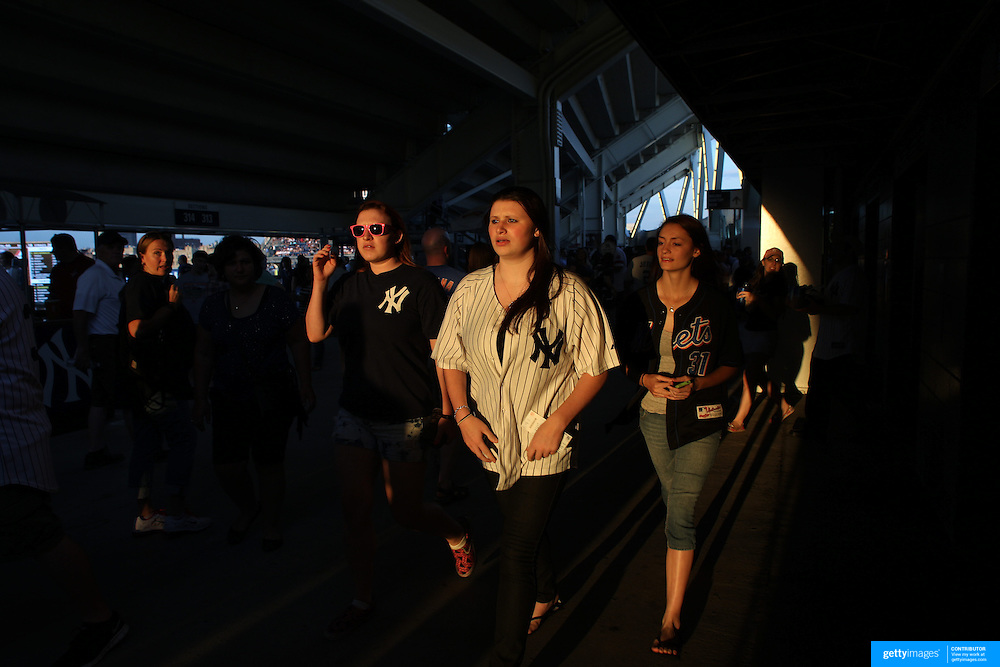 Mets and Yankees fans caught by the setting sunlight behind the stands at Yankee Stadium during the New York Yankees V New York Mets Subway Series Baseball game at Yankee Stadium, The Bronx, New York. 8th June 2012. Photo Tim Clayton