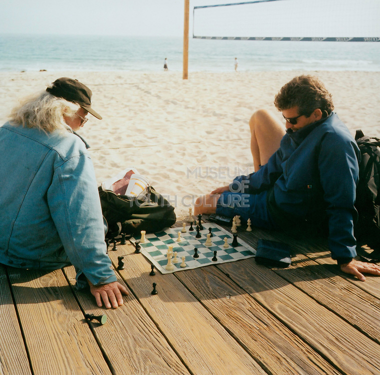 Two men playing chess on the beach, USA
