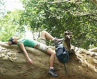 Young woman resting on rock formation in forest side view