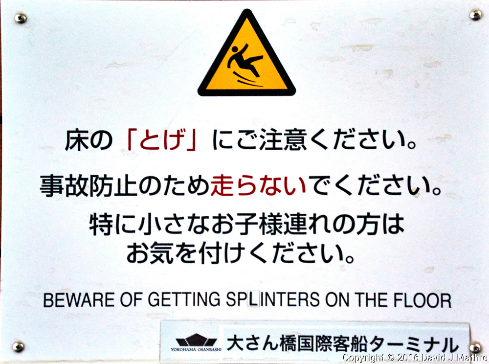 """Beware of Getting Splinters on the Floor"" Warning sign on the  Osanbashi Pier in Yokohama Japan. Image taken with a Nikon 1 V3 camera and 10-30 mm lens (ISO 800, 22 mm, f/4.8, 1/30 sec)."