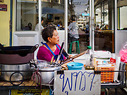 22 DECEMBER 2018 - CHANTABURI, THAILAND: A street food vendor waits for customers in front of a gem cutting shop in the Chantaburi gem market. The gem market in Chantaburi, a provincial town in eastern Thailand, is open on weekends. Chantaburi used to be an active gem mining area in Thailand, but the mines are played out now. Now buyers and sellers come from around the world to Chantaburi for the weekend market. Many of the stones come from Myanmar, others come from mines in Afghanistan and Africa.      PHOTO BY JACK KURTZ