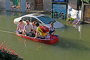 WUHAN, CHINA - JULY 09: <br /> <br /> A man pushes a boat carrying several people in a flooded street on July 10, 2016 in Wuhan, Hubei Province of China. Many parts of Wuhan city have been submerged in floodwaters since July 9, due to torrential rains and flood peaks on the Yangtze river.<br /> ©Exclusivepix Media