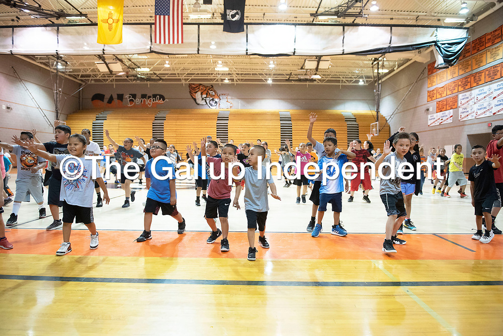 Campers play a game of Coach Says, a basketball version of Simon Says, led by Coach Todd McBroom, Monday, June 3 at the Bengal Basketball Kids Camp at Gallup High School.