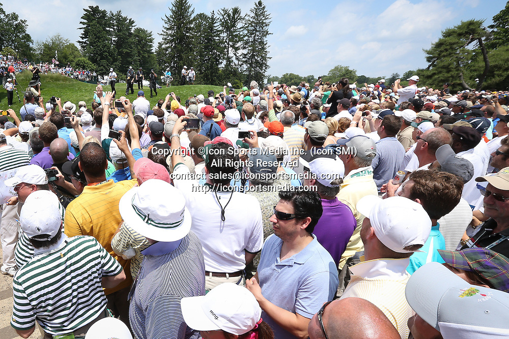June 11 2013: Hundreds of fans try to find a vantage point to see Tiger Woods walk from the 1st hole during tuesday's practice round at the 2013 U.S. Open hosted by Merion Golf Club in Ardmore, PA.