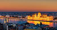 Blick von der Fischerbastei auf die Donau mit dem beleuchtete Parlamentsgebaeude bei Sonnenuntergang.