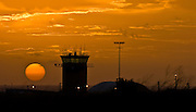 The rising sun coming up next to the Lihue Airport Tower on the island of Kauai, Hawaii