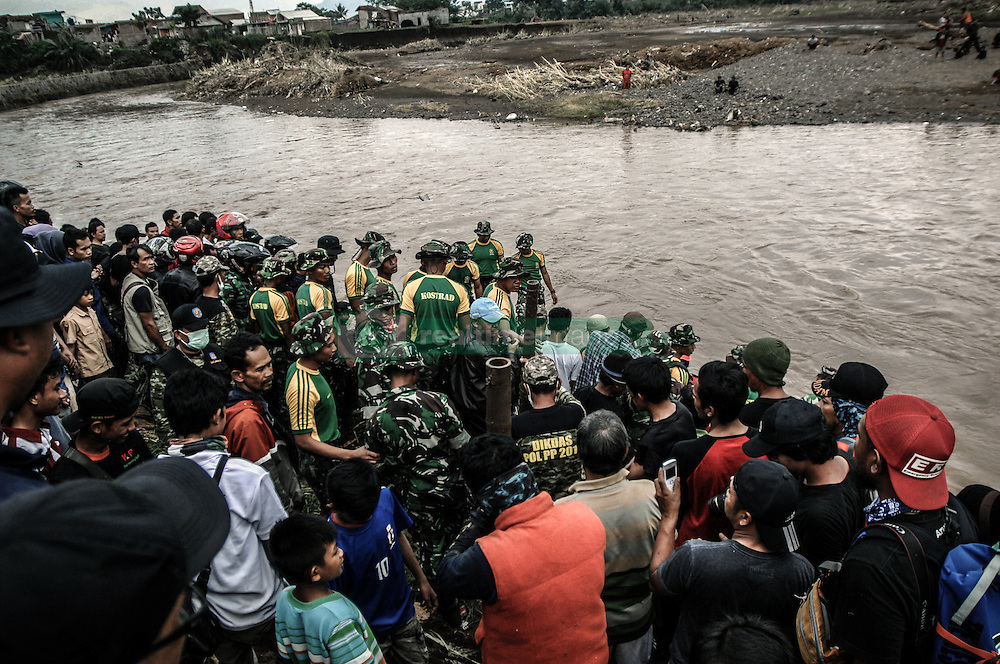 September 23, 2016 - Garut, Indonesia - Soldiers of the Army Strategic Reserve Command and Volunteers search for victims of the flood disaster in a car which was found drifting on the river in Cimacan, Garut, on September, 23.2016. The death toll from devastating floods and landslides in Indonesia has risen to 26, an official said, with hopes fading for 19 others still missing. (Credit Image: © Dasril Roszandi/NurPhoto via ZUMA Press)