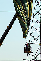 ©Licensed to London News Pictures. 26/03/2012.Bozeat, Northamptonshire. Workmen help remove hotair balloon. A hot-air balloon crashed into power lines in Northamptonshire, trapping a woman and two men 15m in the air.<br /> The balloon's canopy wrapped round live cables just after 18:00 BST on Sunday, at Bozeat near Wellingborough.Photo credit: Steven Prouse/ LNP.