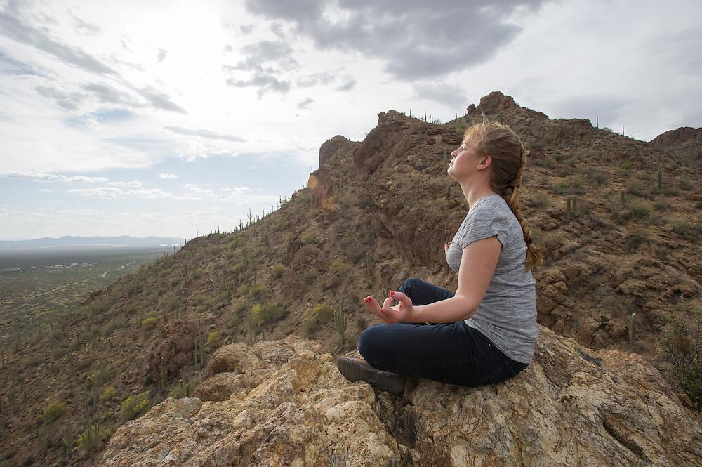 Woman meditating in desert, Tucson AZ