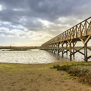 Landmark footbridge heading to famous Quinta do Lago beach, in Ria Formosa wetlands natural conservation region landscape, Algarve. Portugal
