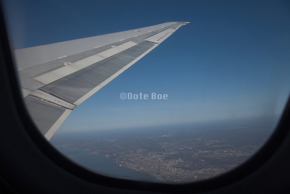 wing of an passenger airplane while in flight above an urban landscape