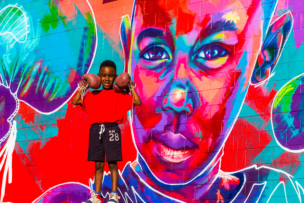 "5 year old Britton Grae-Chapman with boxing gloves in front of a huge mural painted of him by a local artist known as ""Detour"" (actual name Thomas Evans), Denver, Colorado USA."