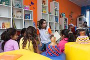 Paula, C&A employee and volunteer, reads to a group of children in the community library, Biblioteca Comunitaria do Arquipelago, Porte Alegre, Brazil. <br /> <br /> Cirandar is working in partnership with  C&A and C&A Instituto to implement a network of Community Libraries in eight communities of Porto Alegre.