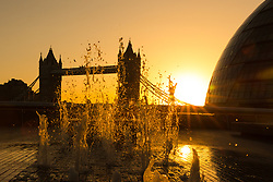 © Licensed to London News Pictures. 03/09/2017. LONDON, UK.  A golden sunrise this morning behind Tower Bridge on the River Thames and City Hall, as the capital wakes up to a chilly and clear autumn morning. Photo credit: Vickie Flores/LNP