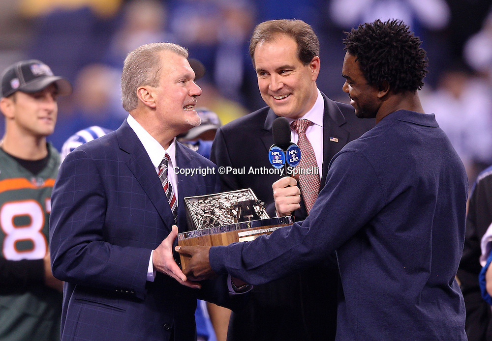 Indianapolis Colts Owner and Chief Executive Officer Jim Irsay (left) accepts the Lamar Hunt AFC Championship Trophy from former Colts running back Edgerrin James (right) while CBS announcer Jim Nantz hosts the postgame trophy presentation after the AFC Championship football game against the New York Jets, January 24, 2010 in Indianapolis, Indiana. The Colts won the game 30-17. ©Paul Anthony Spinelli