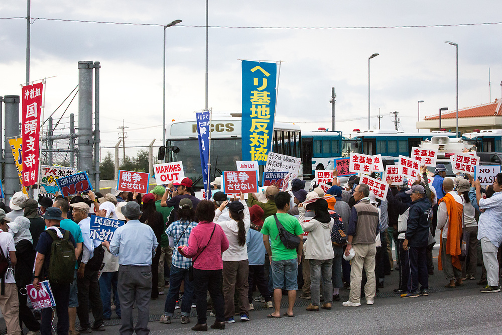 OKINAWA, JAPAN - NOVEMBER 14:  Anti U.S. Base protesters shout with their placards while blocking construction trucks and US marines cars in front of the gate of U.S Marine Base in Camp Schwab, protesting against the construction of the new U.S base in Henoko, Nago, Okinawa prefecture, Japan on November 14, 2015. (Photo: Richard Atrero de Guzman)