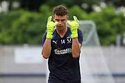 AFC Wimbledon goalkeeper Nicola Tzanev (13) warming up and making sign with hands during the Pre-Season Friendly match between AFC Wimbledon and Bristol City at the Cherry Red Records Stadium, Kingston, England on 9 July 2019.