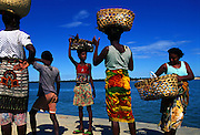 MADAGASCAR: Morondava.Collecting fish in baskets  from fishermen in canoes