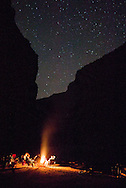 People gathered around campfire under stars in Grand Canyon, AZ