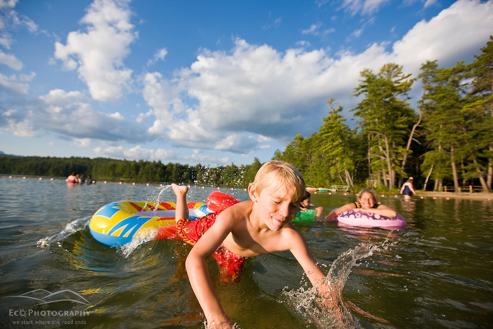 A boy jumps off his floating toy at the beach at White Lake State Park in Tamworth, New Hampshire.