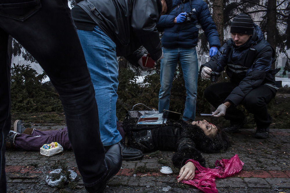 DONETSK, UKRAINE - JANUARY 30, 2015: Investigators examine the body of a woman killed by a rocket attack near a humanitarian aid distribution center in Donetsk, Ukraine. At least five people were killed at the scene, and at least two others died in a separate shelling nearby. CREDIT: Brendan Hoffman for The New York Times