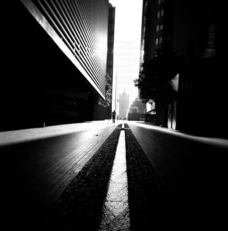 Tall buildings along a street in London with a figure silhouetted