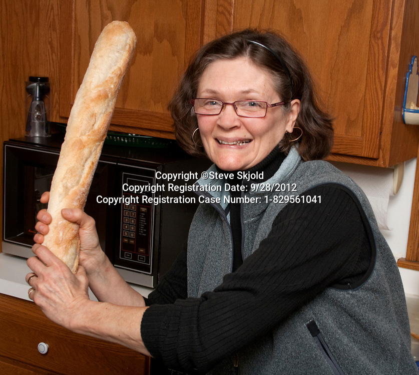 Fun loving hostess playing ball in the kitchen with our baguette dinner bread. St Paul Minnesota MN USA
