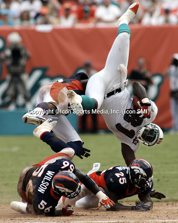 The Miami Dolphins Randy McMichael (81) fly's over  Denver Broncos Al Wilson (51) and Nick Ferguson (25) in the second quarter at Dolphins Stadium in Miami, Florida, SUnday September 11, 2005.