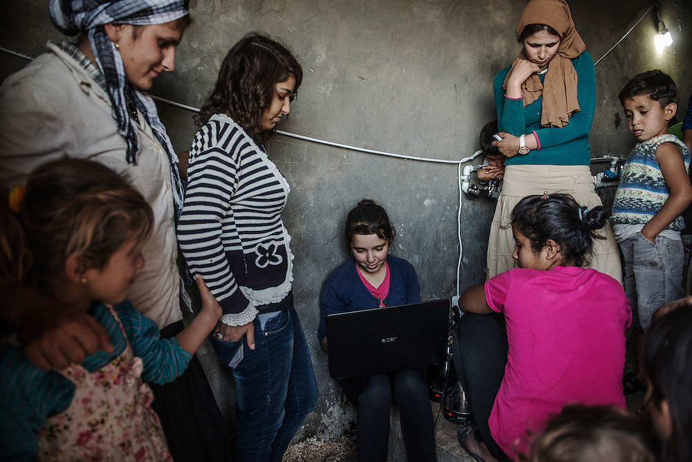 Syrian refugees at the camp in Suruc- Rounaq was using her computer with her friend Anari and other in the bathroom, they have limited power resources. She came 29sep from kobani 15 years.