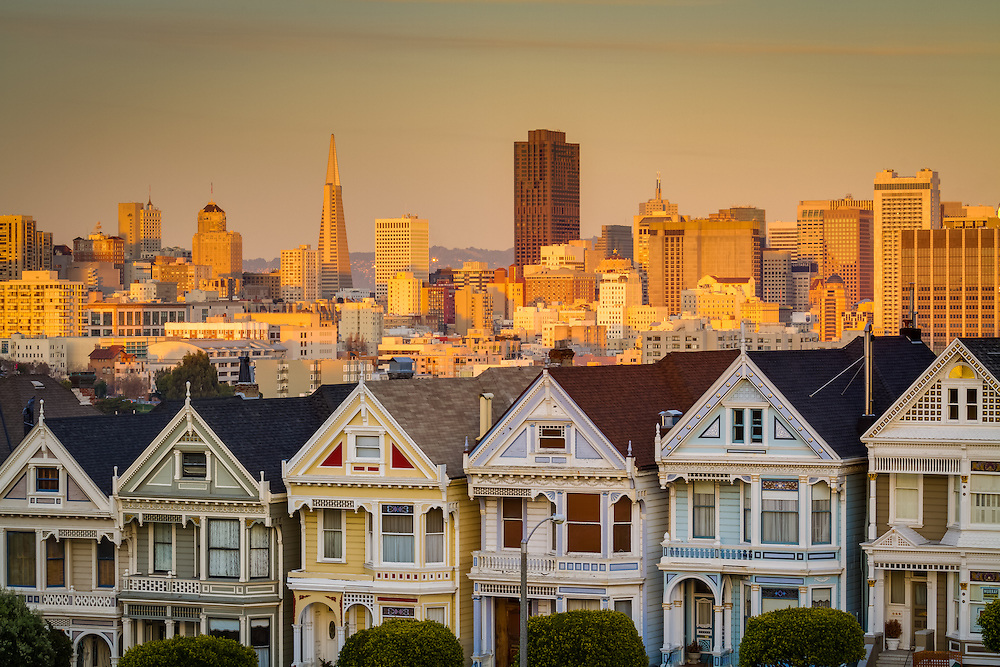 The Painted Ladies, as they are called, in San Francisco's Alamo Square at sunset.  The city skyline provides a great backdrop to these amazing houses.