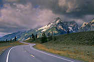 Curving road below mountain range dusted by first snow of fall, Grand Teton National Park, WYOMING