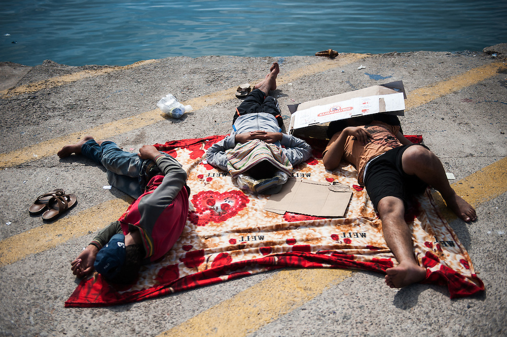 Afghan migrants sleeping at the port of Mytiline waiting for the next available boat tat will take them to the Greek mainland.