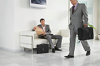 Business man walking past a man reading newspaper in office hallway