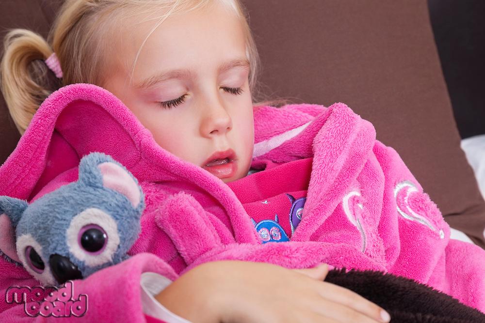 Cute little girl in pink jacket sleeping with teddy bear