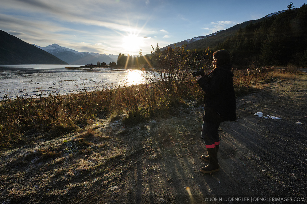 Allison Stuart prepares to photograph birds along Lutak Inlet near Haines, Alaska. Since 2009, students have been conducting a weekly count of bald eagles during the fall semester for the citizen science class at the Haines School. The project is part of a field-based for-credit class, sponsored by the Takshanuk Watershed Council, in which students participate in research studies and learn about field data collection. Under the guidance of Pam Randles, Takshanuk Watershed Council Education Director, students count bald eagles in the Chilkat River Valley using spotting scopes at 10 locations and present their data at the Bald Eagle Festival held in November in Haines. During late fall, bald eagles congregate along the Chilkat River to feed on salmon. This gathering of bald eagles in the Alaska Chilkat Bald Eagle Preserve is believed to be one of the largest gatherings of bald eagles in the world.