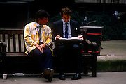 A trader from the LIFFE futures exchange meets an associate in the street during a weekday lunchtime on a bench in the City of London. Talking over paperwork with an opened attache briefacse and wearing the colourful jacket of this once thriving financial institution, we see a scene of wealth and prosperity, from an era of growth during the industrial revolution to the arrogance and self-indulgence during the government of John Major - a political inheritance from Margaret Thatcher. The LIFFE exchange was synonymous with Thatcherite capitalist money-making ethos in the City of London of the 80s and early 90s before the takeover by Euronext in January 2002. It is currently known as Euronext.liffe. Euronext subsequently merged with New York Stock Exchange in April 2007.