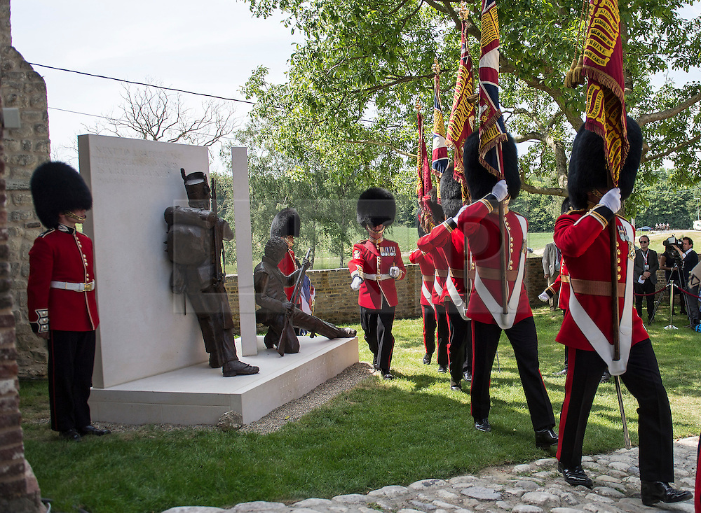 © London News Pictures. 17/06/2015. BELGIUM. <br /> Colour Sergeants march past the new bronze sculpture featuring two British soldiers, by Vivienne Mallock, which was unveiled as a new memorial to all the British dead.. 200 years since the eve of the Battle of Waterloo, Their Royal Highnesses The Prince of Wales and the Duchess of Cornwall attended a special ceremony at Hougoumont Farm, the Belgian Farm Wellington claimed was instrumental in his victory.  Photo credit: Sergeant Rupert Frere/LNP