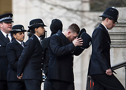 © Licensed to London News Pictures. 14/12/2017. London, UK. A policeman removes his hat as he arrives at St Paul's Cathedral in London for a Grenfell Tower National Memorial Service to mark the six month anniversary of the Grenfell Tower fire. The service is attended by survivors of the fire and relatives of those who lost their lives in the fire, as well as members of the emergency services and members of the Royal family.  Over 70 people were killed when a huge fire ripped though 24-storey Grenfell Tower block in west London in June 2017.   Photo credit: Ben Cawthra/LNP