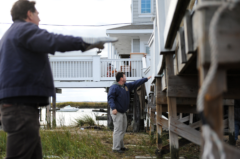 Joe Lane (center) and John Perdoch move to steady Lane's gangway to his house after it was displaced by Hurricane Sandy. Broad Channel, N.Y., Nov. 3, 2012.