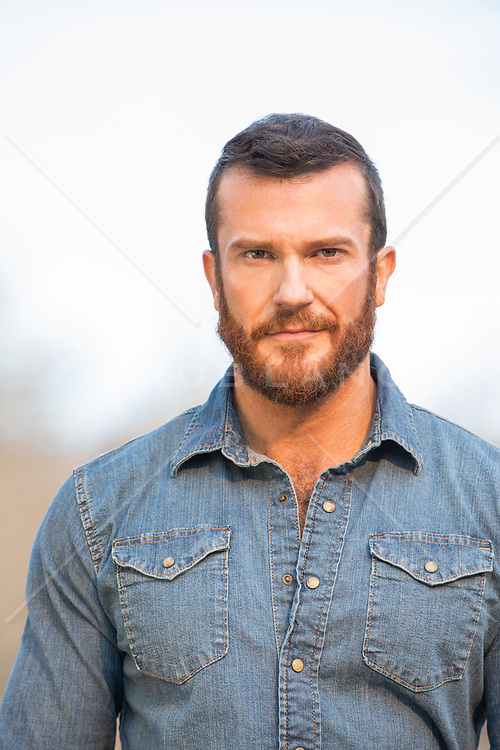 portrait of a good looking bearded 34-40 year old man outdoors