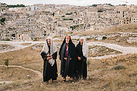 """MATERA, ITALY -6 OCTOBER 2019: The actors performing the roles of the Pharises are seen here in the backstage of """"The New Gospel"""", a film by Swiss theatre director Milo Rau, in Matera, Italy, on October 6th 2019.<br /> <br /> Theatre Director Milo Rau filmed the Passion of the Christ  under the title """"The New Gospel"""" with a cast of refugees, activists and former actors from Pasolini and Mel Gibson's films.<br /> <br /> The role of Jesus is performed by Yvan Sagnet, a Political activist born in Cameroon and who worked on a tomato farm when in 2011 he revolted against the system of exploitation and led the first farm workers' strike in southern Italy. In a series of public shoots in the European Capital of Culture Matera, Jesus will proclaimed the Word of God, was crucified (October 6th 2019) and finally rose from the dead in Rome, the capital of Catholic Christianity and seat of one of the most xenophobic governments in Europe (October 10th 2019).<br />  <br /> Parallel to the film, the humanistic message of the New Testament was transformed into the present: at the beginning of September, the campaign """"Rivolta della Dignità"""" (Revolt of Dignity), which demanded fair working and living conditions     for refugees, global freedom of travel and civil rights for all, started with a march from the southern Italian refugee camps. """"It's about putting Jesus on his feet,"""" director Milo Rau said. Led by Jesus actor Yvan Sagnet, the campaign fights for the rights of migrants who came to Europe via the Mediterranean to be enslaved by the Mafia in the tomato fields of southern Italy and to live in ghettos under inhumane conditions. The campaign and the film thus create a """"New Gospel"""" for the 21st century, a manifesto of solidarity with the poorest, a revolt for a more just and humane world."""