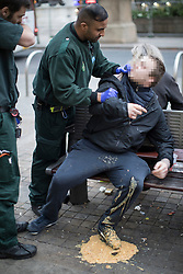 © Licensed to London News Pictures . 06/04/2017 . Manchester , UK . A paramedic tends to a man who has vomited over himself , on a bench on Piccadilly . An epidemic of abuse of the drug spice by some of Manchester's homeless population , in plain sight , is causing users to experience psychosis and a zombie-like state and is daily being witnessed in the Piccadilly Gardens area of Manchester , drawing large resource from paramedic services in the city centre . Photo credit : Joel Goodman/LNP