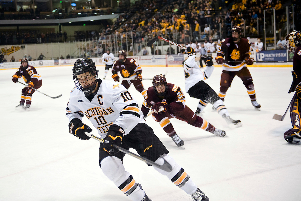 HOUGHTON, MI -DEC. 12, 2014: Michigan Tech player Tanner Kero, number 10, skates toward the puck with Austyn Young, number 23, of Minnesota Duluth coming from behind Friday, Dec. 12, 2014 at MacInnes Student Ice Arena in Houghton, MI. Lauren Justice for The New York Times