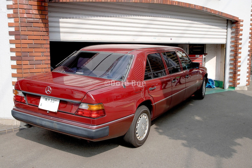 double length Mercedes Benz parked halve under the door of a much to small garage