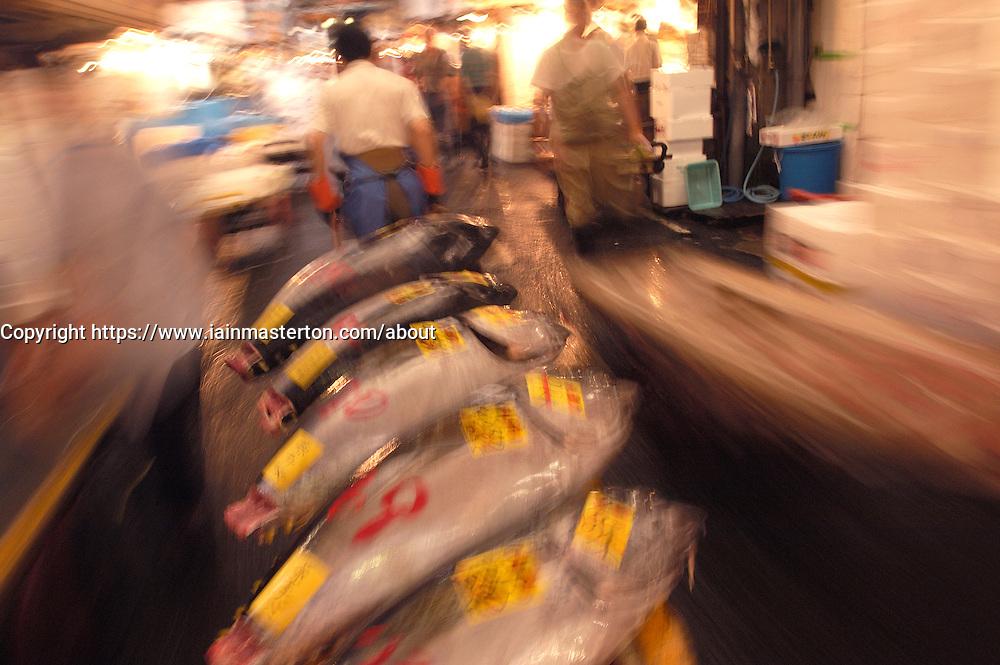 Transporting barrow of fresh tuna at Tsukiji fish Market in Tokyo motion blur