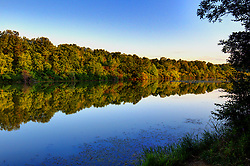 18 July 2014: Light at near dusk attempts to change the color of the trees that line the banks of  Dawson Lake located in Moraine View State Park maintained by the Illinois Department of Natural Resources (IDNR) near Le Roy Illinois This images has been created in part using High Dynamic Range (HDR) or Panoramic Stitching processes.