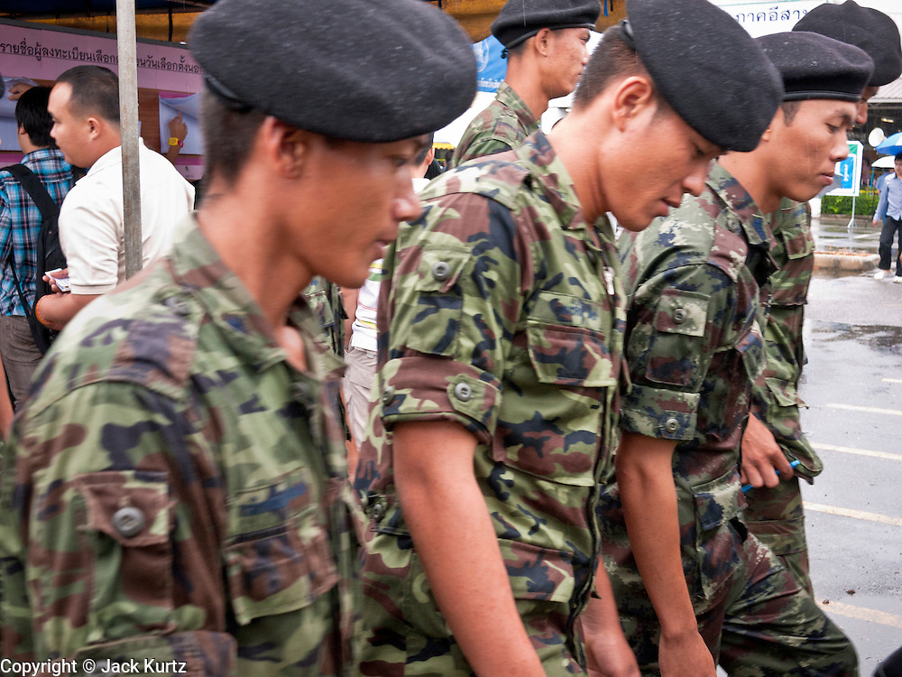 26 JUNE 2011 - CHIANG MAI, THAILAND:   Thai soldiers walk in the voting center in Chiang Mai, Thailand, to cast their absentee ballots Sunday. The role of the military in this election has been fiercely debated because the Army command has indicated they would not favor a victory by Pheua Thai, the leading party in this election. Absentee voting was Sunday, July 26 in Thailand's national election. The regular voting is Sunday July 3. In Chiang Mai, center of the powerful Red Shirt opposition movement and their legal party Pheua Thai, turnout was heavy despite a steady rain. Thailand's democracy will be tested in the election, which is the most bitterly fought contest in Thai political history. The Pheua Thai represents people loyal to fugitive former Prime Minister Thaksin Shinawatra, ousted by a military coup in 2006. The ruling Democrats have governed Thailand in one form or another nearly continuously since 1932. Pre-election polls show Pheua Thai leading but not by enough to rule without forming a coalition with smaller parties.   PHOTO BY JACK KURTZ