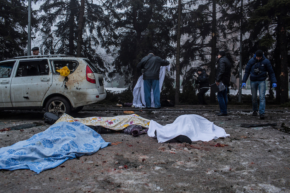 DONETSK, UKRAINE - JANUARY 30, 2015: Investigators examine the bodies of four people who were killed when a rocket struck the parking lot outside a center where humanitarian aid was being distributed in Donetsk, Ukraine. A fifth person was killed in a parked car, and at least two others died in a separate shelling nearby. CREDIT: Brendan Hoffman for The New York Times