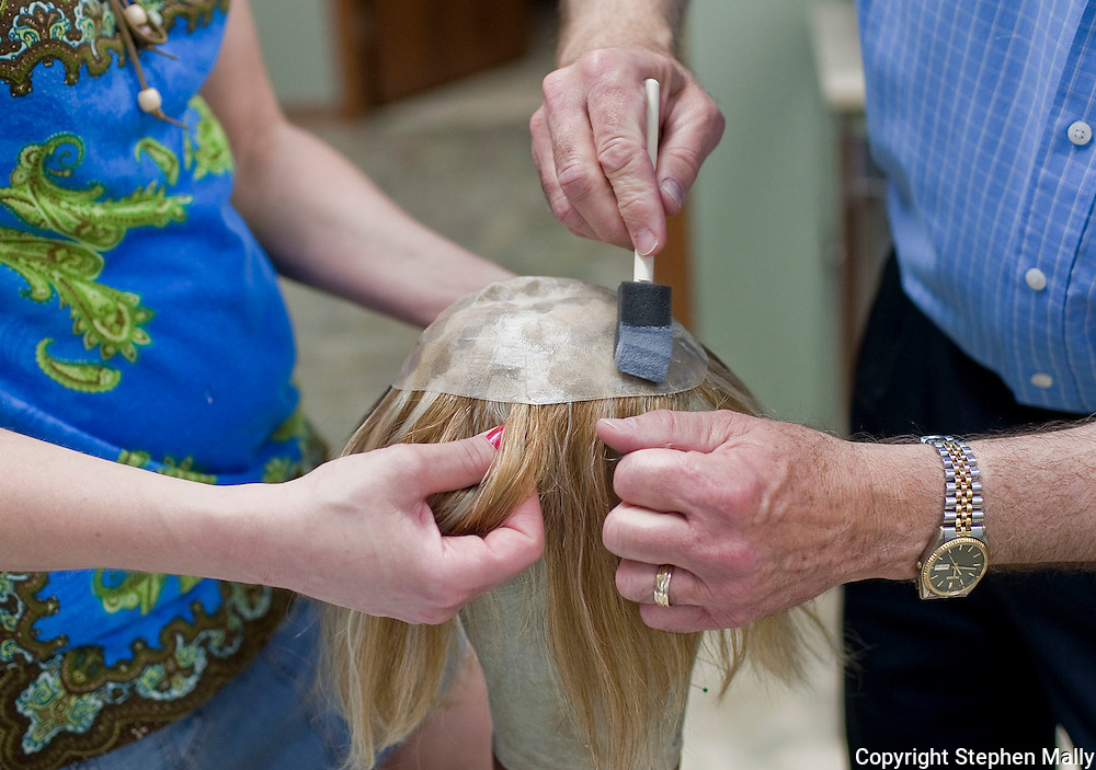 Daryl Grecian (right), of Solon, applies adhesive as his assistant, D Vizecky, of Cedar Rapids, holds the hair at Advanced Hair Technologies in Hiawatha on Saturday, May 29, 2010.